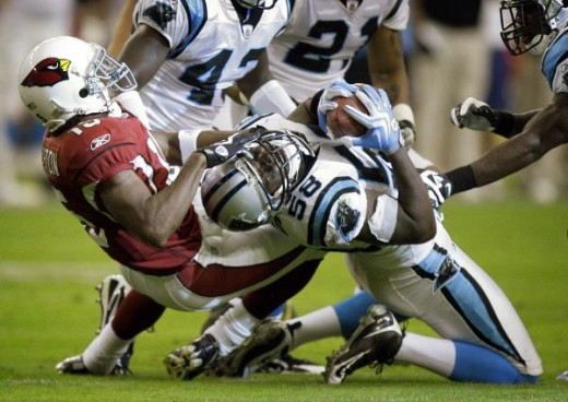 Carolina Panthers linebacker Thomas Davis (58) intercepts a pass intended for Arizona Cardinals wide receiver Steve Breaston (15) during the first half of an NFL football game Sunday, Nov. 1, 2009, in Glendale, Ariz. (AP Photo/Paul Connors)
