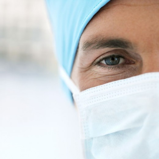photo of a surgeon with a surgical cap and mask