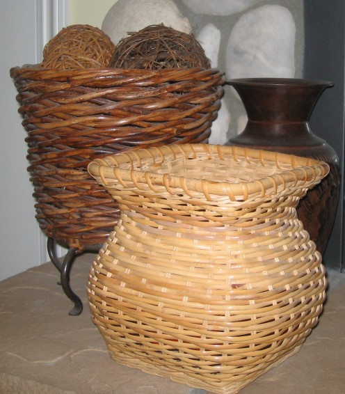 Two wicker baskets and one metal vase in varying degrees of darkness and heights.