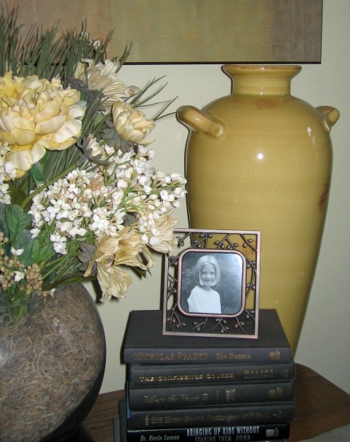Pottery, books, picture and floral all grouped together in colors that blend.