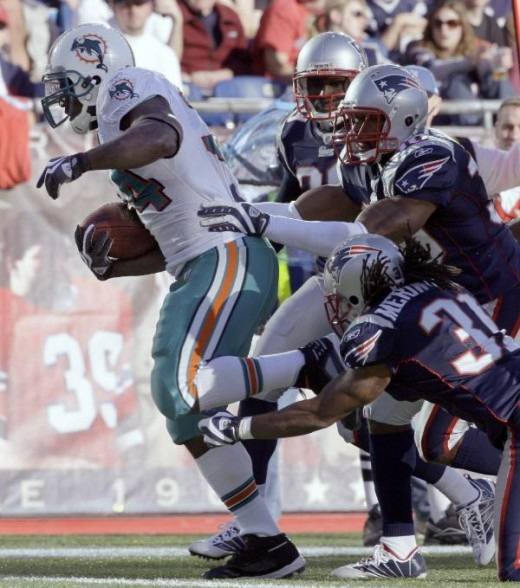 Miami Dolphins running back Ricky Williams, left, scrambles into the end zone for a touchdown during the second quarter of an NFL football game against the New England Patriots. Sunday, Nov. 8, 2009. (AP Photo/Charles Krupa)