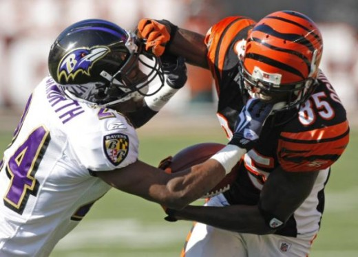 Cincinnati Bengals receiver Chad Ochocinco (85) is tackled by Baltimore Ravens cornerback Domonique Foxworth (24) in the first half of an NFL football game, Sunday, Nov. 8, 2009, in Cincinnati. (AP Photo/Ed Reinke)