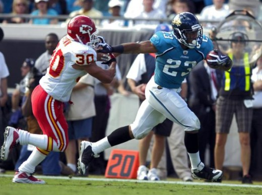 Jacksonville running back Rashad Jennings, right, stiff-arms Kansas City safety Mike Brown for a touchdown in first quarter game action during an NFL football game, Sunday, Nov. 8, 2009, in Jacksonville, Fla. (AP Photo/Stephen Morton)