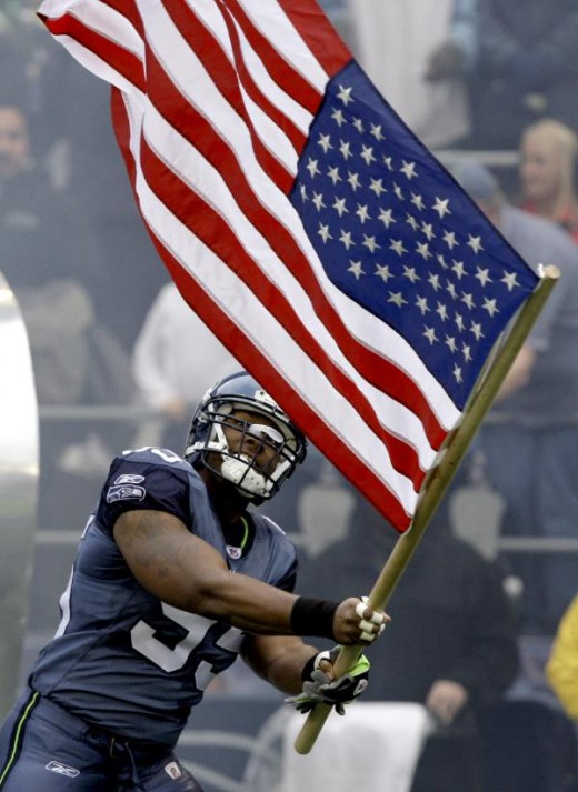 Seattle Seahawks' Lawrence Jackson waves a U.S. flag on military appreciation day before the Seahawks' NFL football game against the Detroit Lions on Sunday, Nov. 8, 2009, in Seattle. (AP Photo/Elaine Thompson)