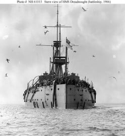 The HMS Dreadnought at sea. Note the seagulls all around the ship.