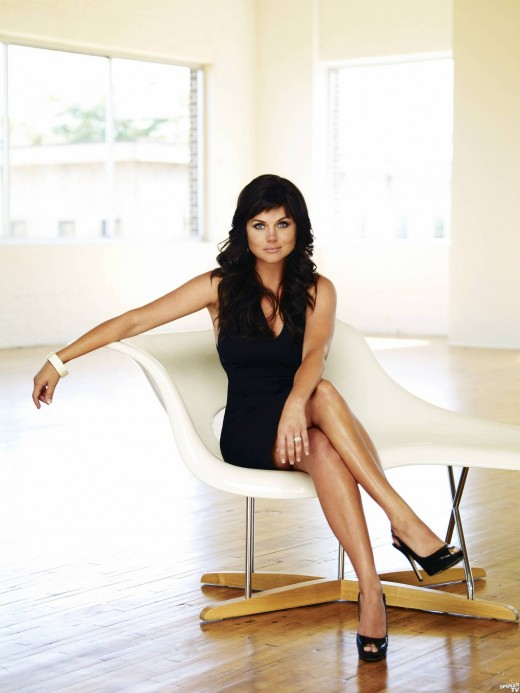 Tiffani Thiessen in a little black dress and high heels crosses her legs for a 'White Collar' promo shoot.