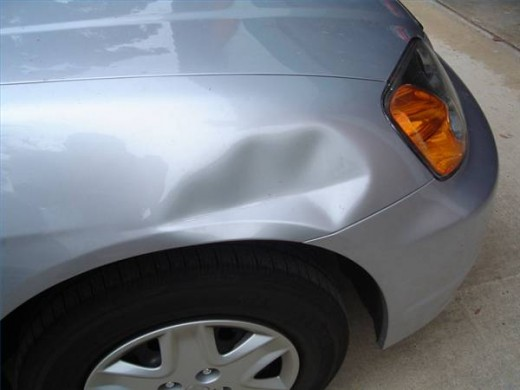 Car dent.  Lucky for this guy, no paint was damaged.  This is an easy fix.