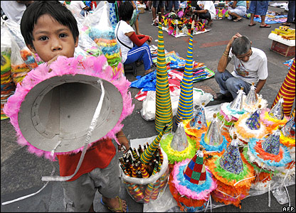 Man selling paper hats for New Year celebration bbc.co.uk