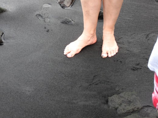 My wife's bare feet in the black sand.  Note the course grain of the sand.