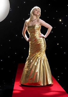 full length, boned, strapless dress is made in eye-catching metallic lycra which wraps around the dress and is rouched at the side seam to add depth and texture.