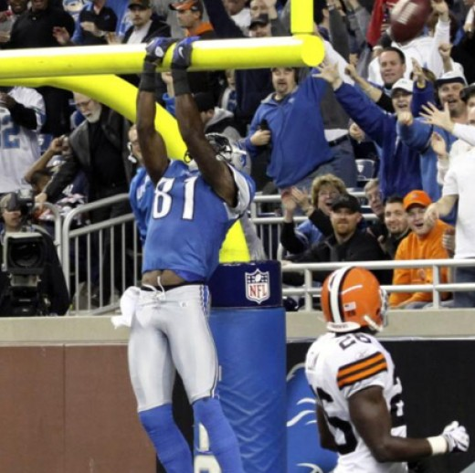 Cleveland Browns defensive back Abram Elam (26) watches as Detroit Lions receiver Calvin Johnson (81) tosses the ball over the goalpost after scoring a touchdown during the second quarter of an NFL football game in Detroit, Sunday, Nov. 22, 2009. (AP