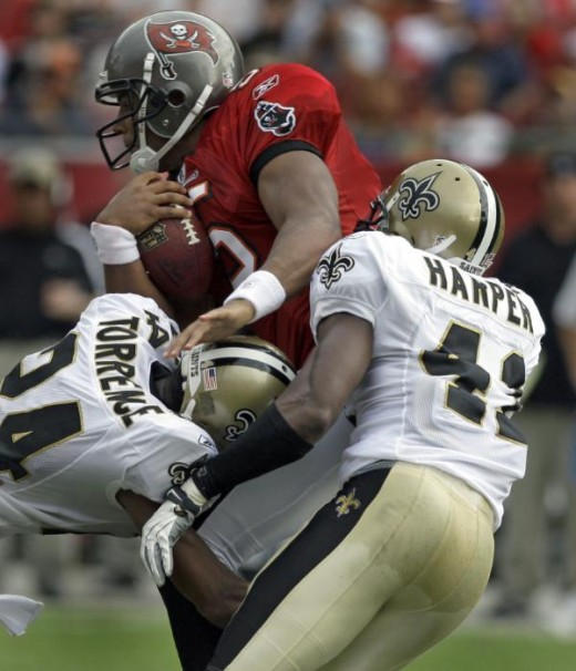 Tampa Bay Buccaneers quarterback Josh Freeman, center, is sacked by New Orleans Saints cornerback Leigh Torrence, left, and safety Roman Harper in the first half of an NFL football game in Tampa, Fla., Sunday, Nov. 22, 2009. (AP Photo/John Raoux)