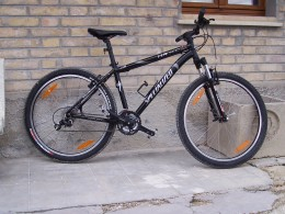 Typical reasonable quality MTB by Specialized; their Hardrock series. The frame is reasonably light and there is front suspension for bumpy roads. The tyres are full mud off-road tyres; note the lack of mudgards. It's a very good bike for teenagers w
