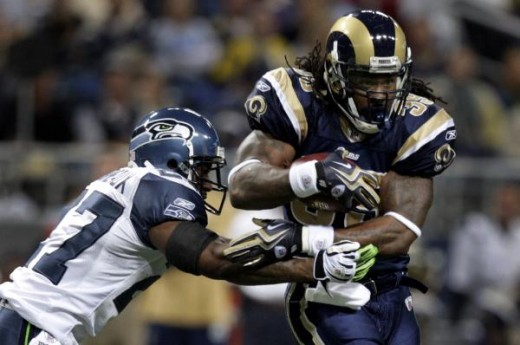 St. Louis Rams running back Steven Jackson, right, runs for a short gain before being brought down by Seattle Seahawks safety Jordan Babineaux during the first quarter  (AP Photo/Jeff Robers)