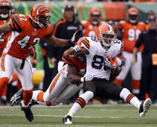 Cleveland Browns wide receiver Chansi Stuckey, right, is dragged down by Cincinnati Bengals' Chinedum Ndukwe as Ndukwe's teammate Chris Crocker (42) looks on during the first half of their NFL football game in Cincinnati, Sunday, Nov. 29, 2009. (AP P