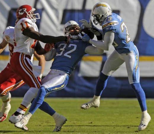 San Diego Chargers' Eric Weddle (32) and Quentin Jammer, right, battle for an interception that Jammer eventually retained as Kansas City Chiefs wide receiver Chris Chambers, left, watches during the first quarter of an NFL football game Sunday, Nov.