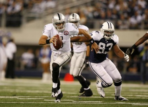 Bruce Gradkowski (5) runs away from Dallas Cowboys linebacker Anthony Spencer (93) in an NFL football game, Thursday, Nov. 26, 2009 in Arlington, Texas. (AP Photo/Mike Stone)
