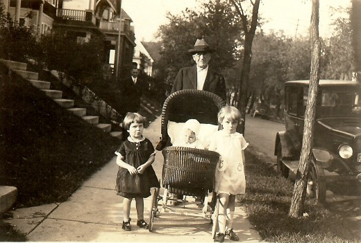 My mother is in the baby carriage with her maternal grandfather pushing the carriage.  He lived with my mother's family in his later years.  Her sister on the right and a little friend (left) are walking alongside the carriage.
