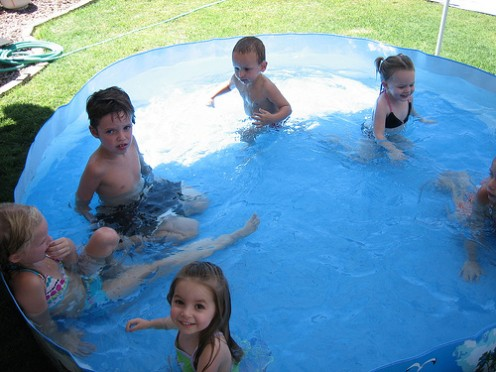 Kids swimming in pool on hot day