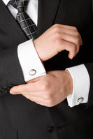 Elegant cuff links on white shirt and dark jacket