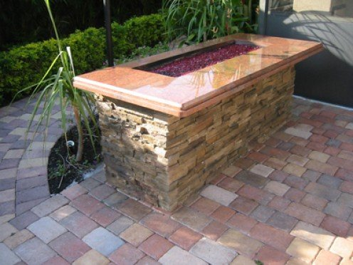 Custom built fire pit uses crushed fire glass.