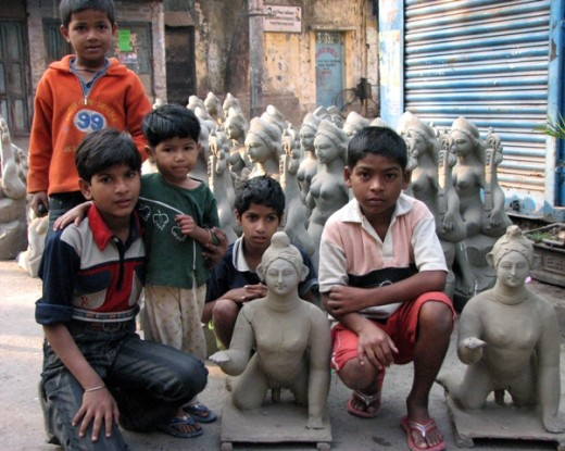 Children @ Potters' colony in Calcutta. Two idols of 'Balagopala' in forefront while those of Saraswati drying in the atmosphere  in the  background.