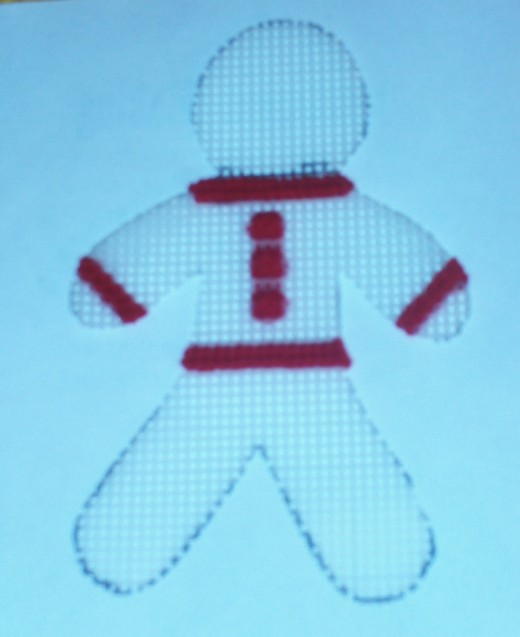 Here I cross stitched three buttons onto the gingerbread man's sweater.