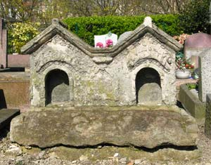 A dog rests behind each door of these dog houses at the Cimetière des Chiens.
