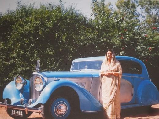Maharani Gayatri Devi standing near a car