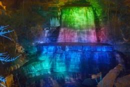 Albion Falls at night under colored spotlights.