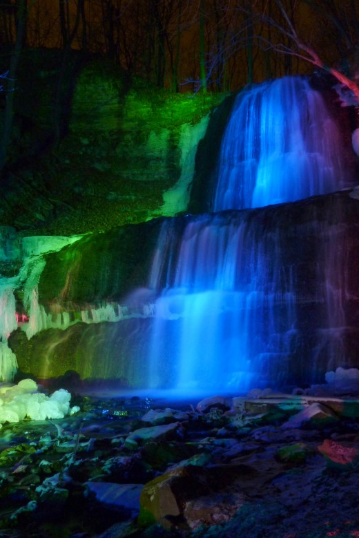 Sherman Falls at night under colored spotlights.