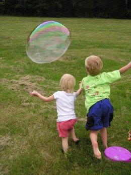 Children chase a bubble.