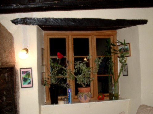 An oak window recently replaced. The beams above the window are original.