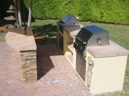 stainless steel charcoal bbq and gas grill built into outdoor kitchen