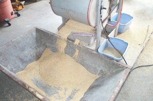The grain spills from one screen to another (each with different sized holes), until it falls at the last into a hopper or other container, and is finished.