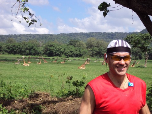 Andrei after cycling all the way to Arusha National Park.  Note the giraffe behind him, exhausted after his effort