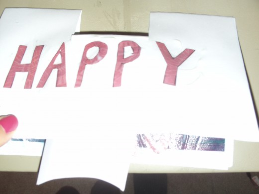 Here I sketched out the word happy on pink paper and cut it out.  Next, I glued it to the front of the card.