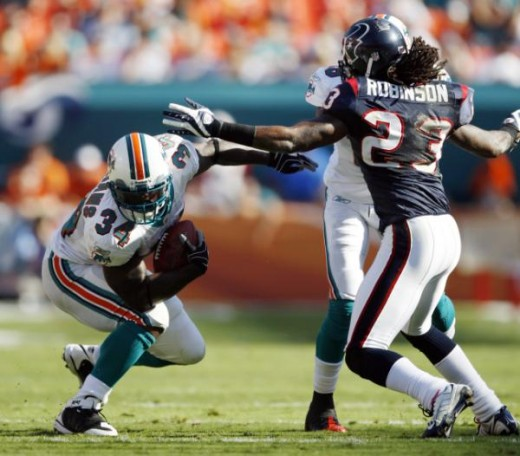Miami Dolphins running back Ricky Williams (34) runs in the second quarter as Houston Texans' Dunta Robinson (23) defends during an NFL football game in Miami, Sunday, Dec. 27, 2009. (AP Photo/Wilfredo Lee)