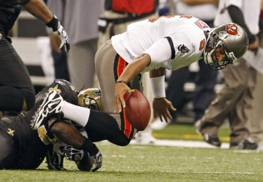 Tampa Bay Buccaneers quarterback Josh Freeman (5) recovers his own fumble as he is sacked by New Orleans Saints defender Mike McKenzie, left, in the first half of their NFL game at the Superdome in New Orleans, Sunday, Dec. 27, 2009. (AP Photo/Dave M