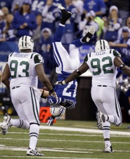 Indianapolis Colts wide receiver Austin Collie, center, flips over after he was hit, between New York Jets defensive ends Marques Douglas, left, and Shaun Ellis during the first quarter of an NFL football game in Indianapolis, Sunday, Dec. 27, 2009.