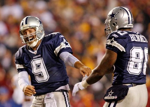 Tony Romo smiles as he runs off the field after the NFL football game against the Washington