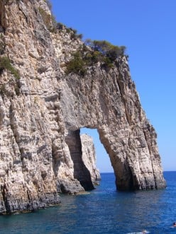 Photo: An arch way formed by the sea in the rock, off the coast of a Greek island.