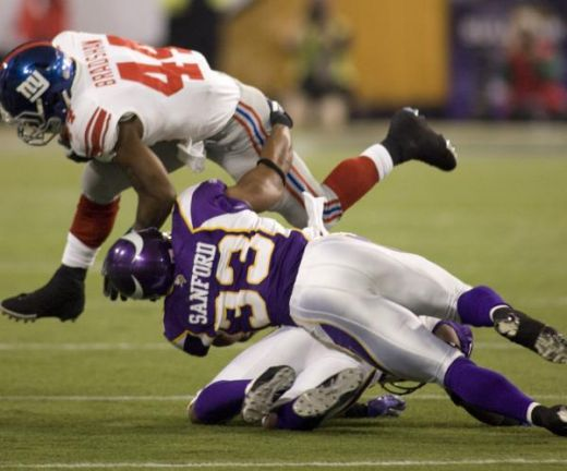 New York Giants running back Ahmad Bradshaw runs into Minnesota Vikings safety Jamarca Sanford, right (33), and Minnesota Vikings cornerback Antoine Winfield in the second quarter as Minnesota Vikings defeated the Giants 44-7 in an NFL football game