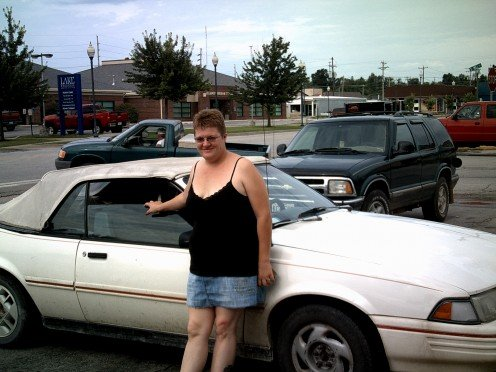 My wife, Georgiana, posing by my first convertible on our vacation last summer.