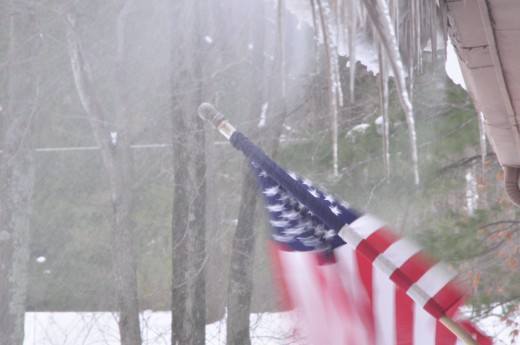 Snow blows off the roof and the wind that carries it ruffles the flag.