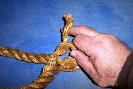 Take the strand next to first one, twist apart the shaft and push the second strand from end of the rope under the raised loop.