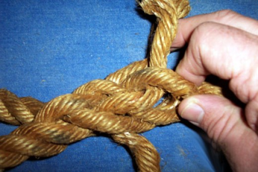 Take the first end strand over the shaft strand next to where it emerges from the shaft, twist up the shaft and push it under the next strand.