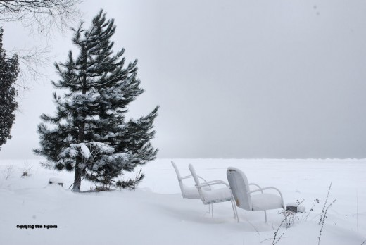 White chairs line a Whitefish Bay beach white with snow overlooking the iced-over bay.