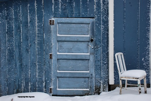 The blue paint of a U.P. outbuilding shows white of snow and frost on a near-zero morning.