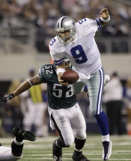 Dallas Cowboys quarterback Tony Romo (9) leaps to evade being tackled as Philadelphia Eagles linebacker Tracy White (52) gives chase in the first half of an NFL wild-card playoff football game, Saturday, Jan. 9, 2010, in Arlington, Texas. (AP Photo/D